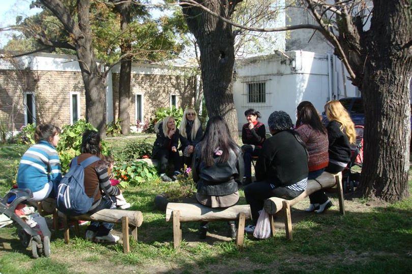 Grupo de personas sentadas de espaldas en una reunión en un jardín.