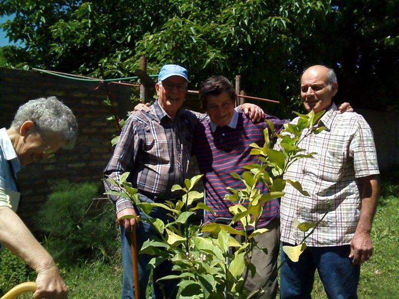 Cuatro señores sonrientes al aire libre.