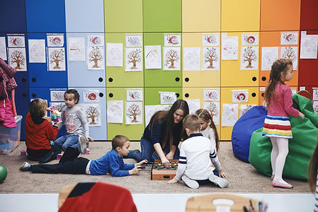 A teacher teaching students in a elementary school with a background of colourful lockers.