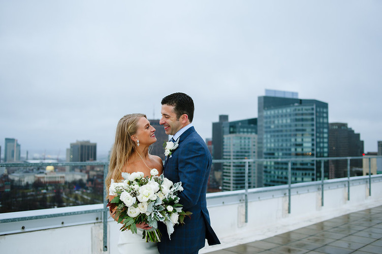Bride and groom outside in city holding bouquet