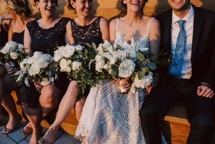 Bridal party sitting in a row holding bouquets