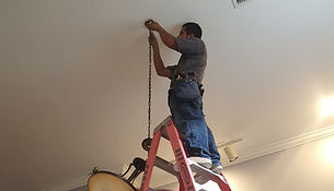Ram electric service technition on ladder hanging light fixture