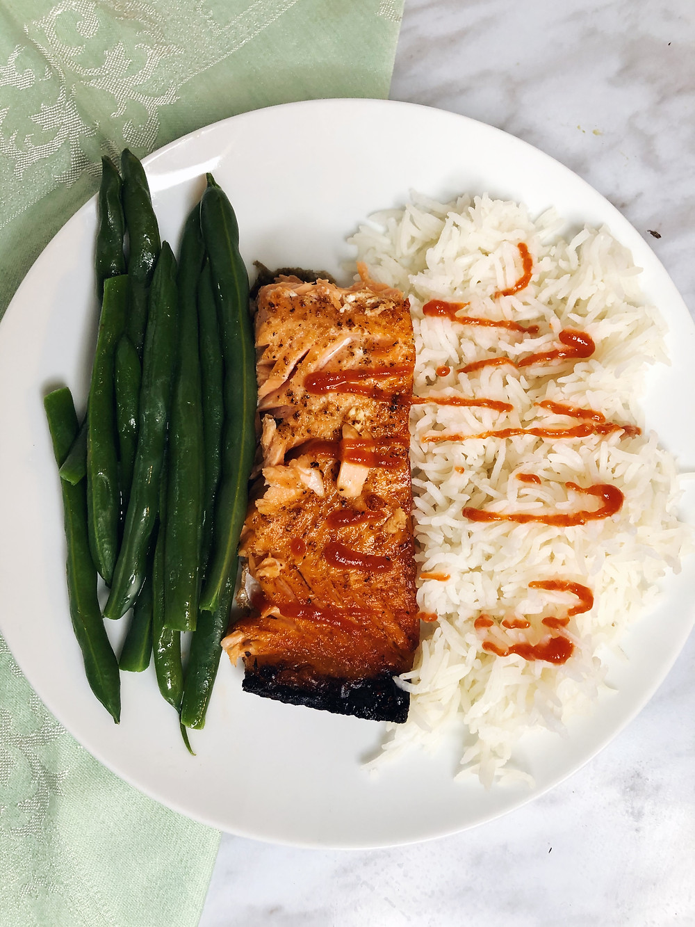 Salmon, green beans and rice with sriracha. The salmon contains a good amount of omega 3s
