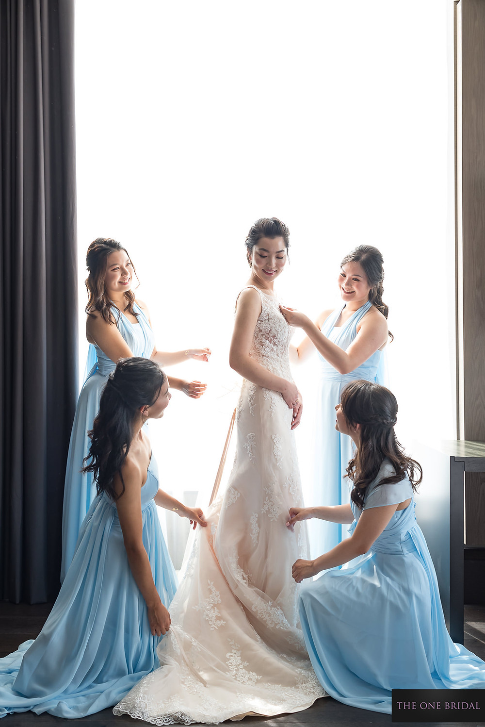 Bridesmaids and Bride putting the wedding dress up