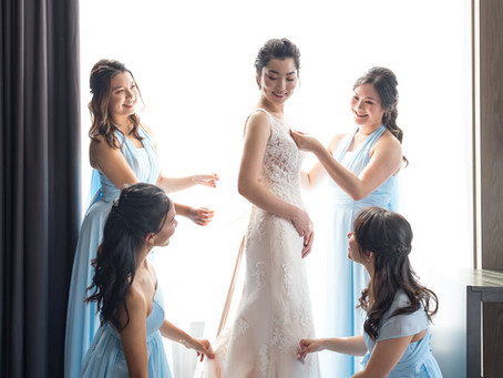 Bridesmaids and Bride Putting Up the Wedding Dress
