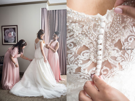 The bride is getting her wedding dress up with her bridesmaids