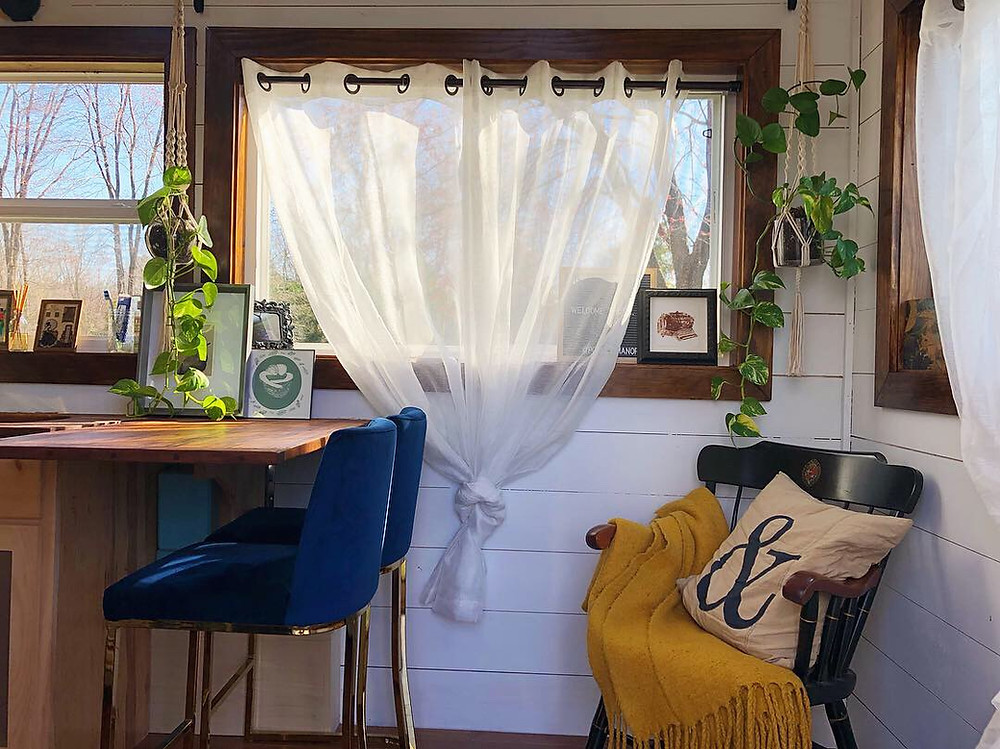 tiny house living room area sunshine windows curtains blue bar stools butcher block countertop painted wood walls hanging plants