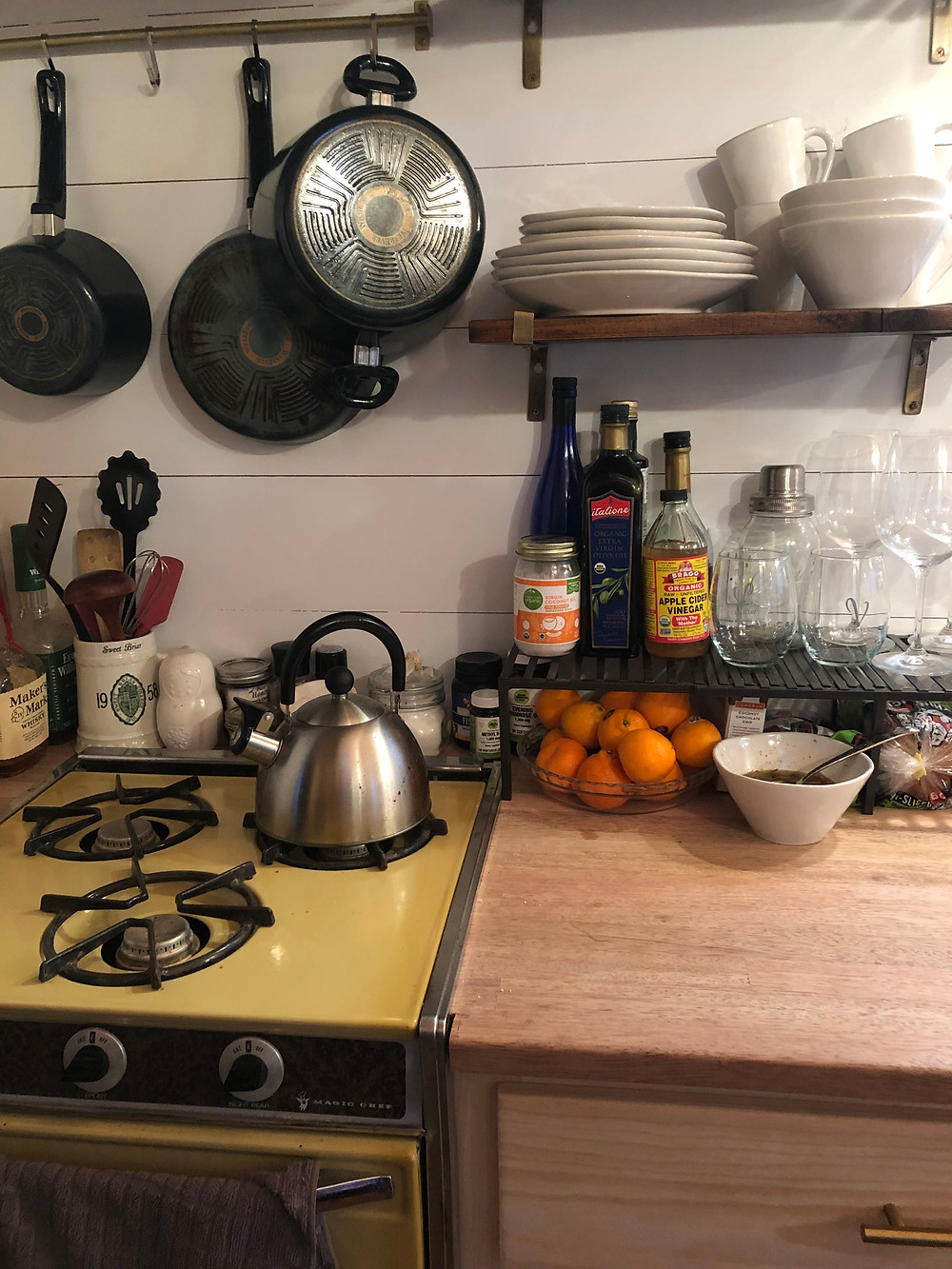 tiny house kitchen vintage stove oven pot hanging racks open shelving tea kettle butcher block countertops