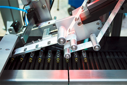 Fully automatic labelling system for labelling horizontal, cylindrical ampoules