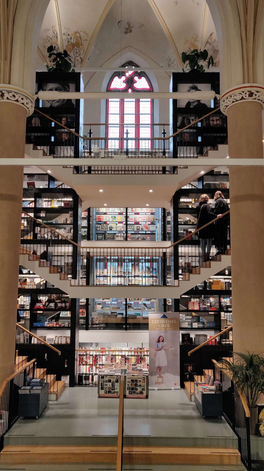 חנות הספרים בתוך מבנה של כנסייה עם ציורי קיר וחלונות ויטראז