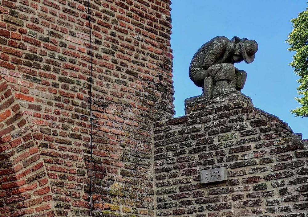 פסל של איש כורע לעשות את צרכיו על שער העיר העתיקה האטם