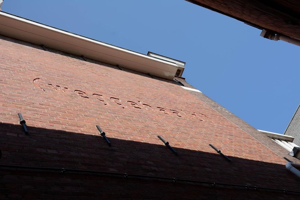 """המילה """"נלקחו"""" בהולנדית על קיר בית בשכונה היהודית"""