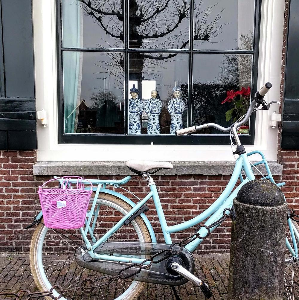 חלון. על אדן החלון שלושה פסלונים של סינים. מלפנים-אופניים נשענים על הבית