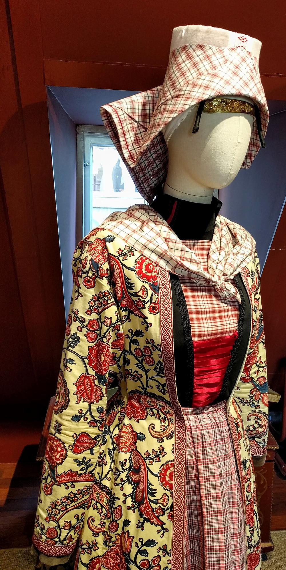. לבוש חגיגי מהינדלופן. אשה לבשה מעיל ארוך מבד רקום וכיסוי ראש מבד משובץ. כיסוי ראש נוקשה חבשו רק נשים נשואות