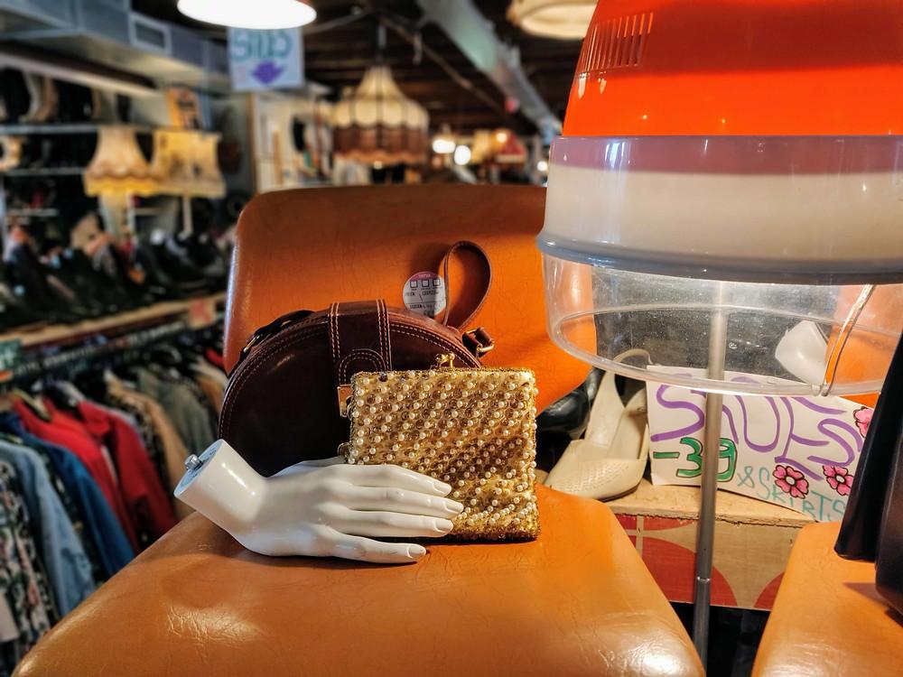 חנות יד שניה. שני ארנקים, יד של בובת תצוגה מפלסטיק מונחים על כסא כתום