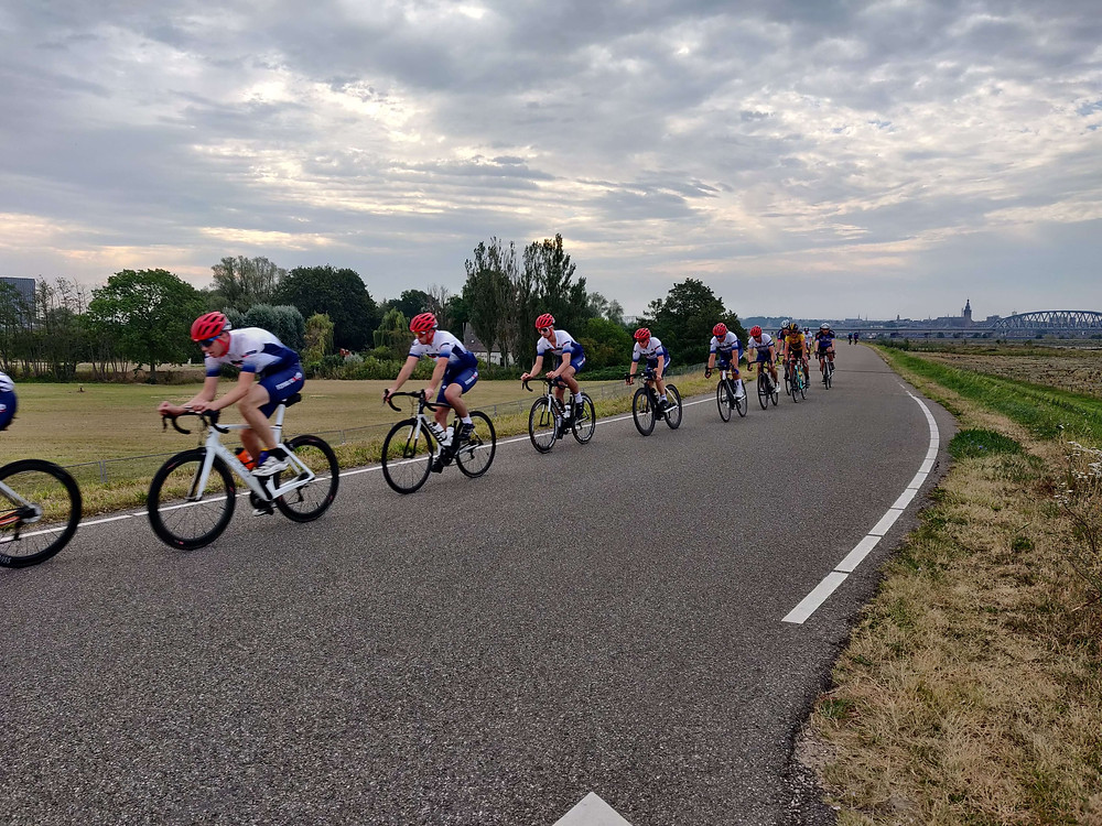 קבוצת אנשים רוכבים על אופניים בבגדי ספורט וקסדות אדומות