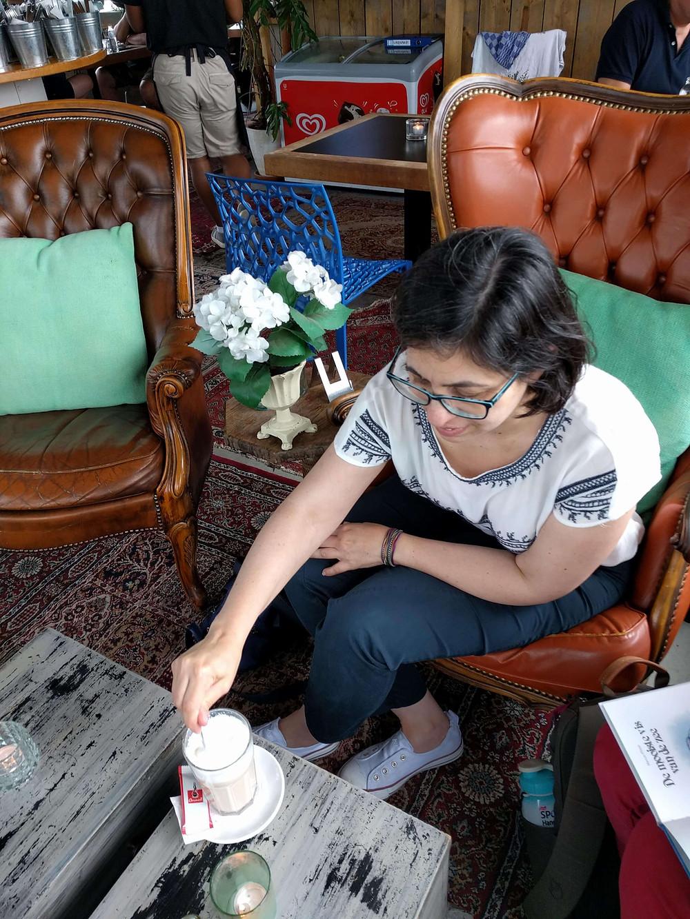 רחלי יושבת בבית קפה