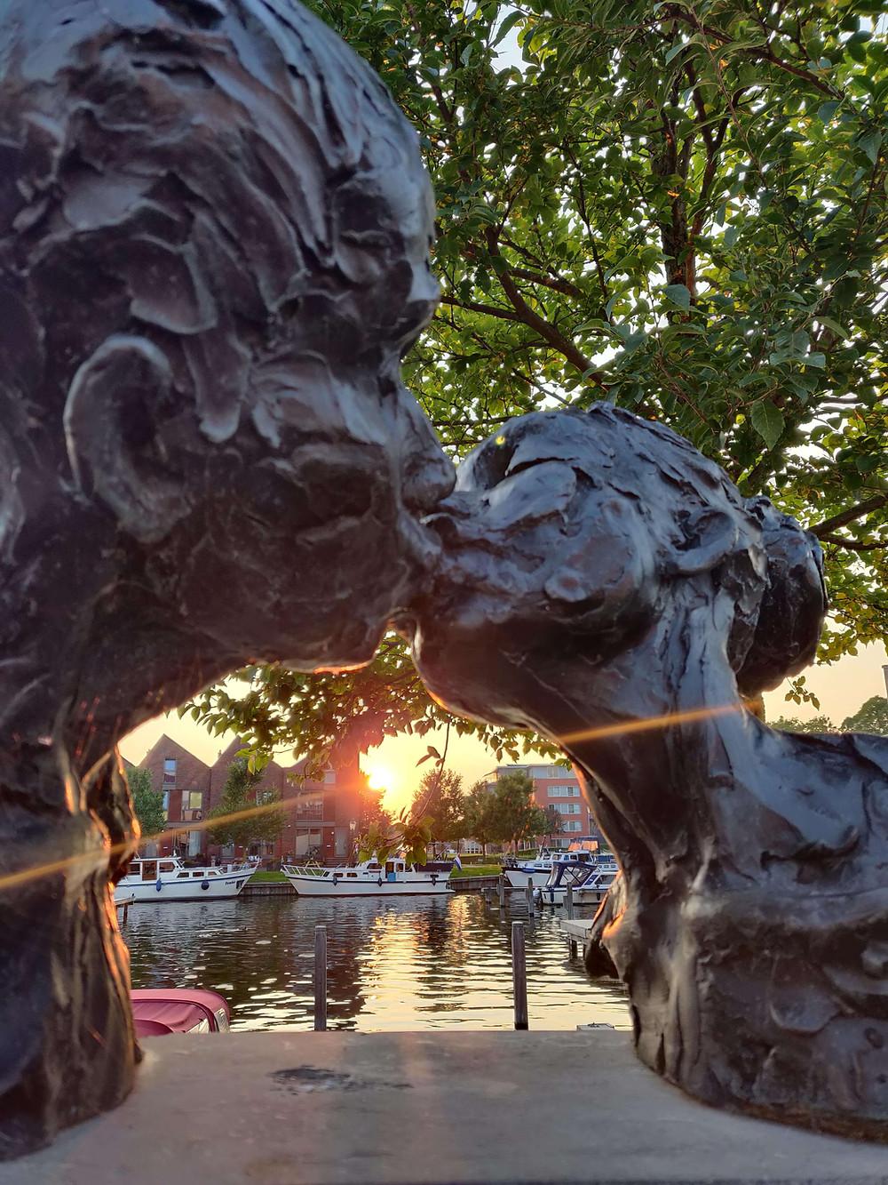 פסל של זוג מתנשק וברקע הנמל
