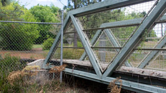 A pedestrian footbridge made inaccessible by the perimeter fence of the Blue Mountains Botanic Gardens.