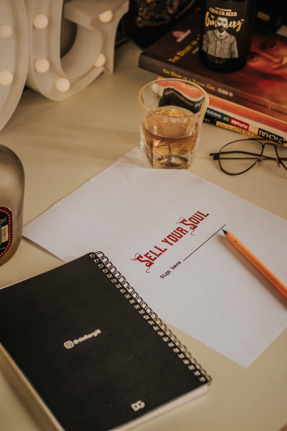 A glass of alcohol, spectacles, a notepad and a paper asking to sell your soul