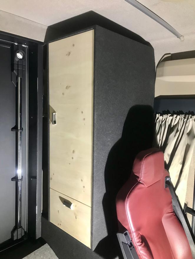 Garderobenschrank und Schublade für Schuhe. Auf dem Element ist Platz für eine Tagesdecke. Zwischen Schrank und Wand sind Schirme und Wanderstöcke verstaut.
