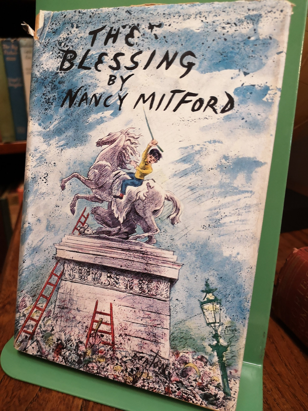 Illustrated front cover of a boy on a horse statue of The Blessing by Nancy Mitford