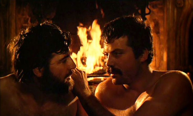 The actors Alan Bates and Oliver Reed are sitting in front of a roaring fire, topless. Oliver Reed has his hand on Alan Bates shoulder.