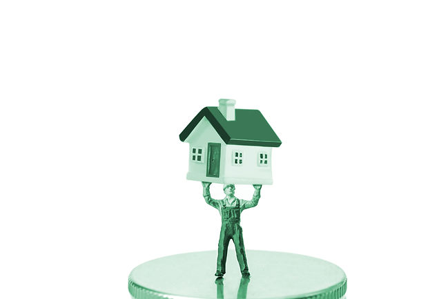 green miniature construction worker holding house on coin