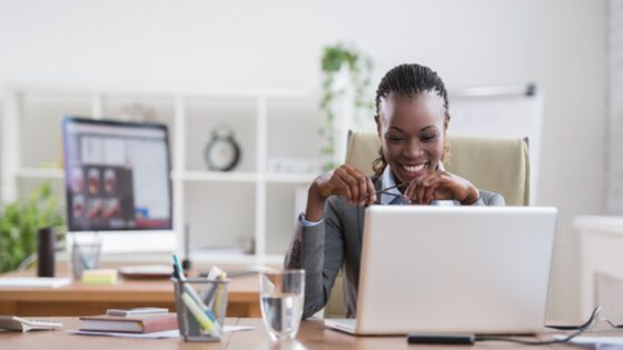 A smiling woman sitting at her desk, concentrating on the work she's doing on her computer
