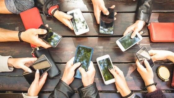 eight people sitting at a picnic table, all looking at their cell phones