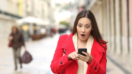 A woman in a red coat, walking down the street looking at her cell phone. She has an expression of surprise or shock on her face.