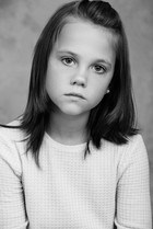 stoic portrait of a young girl in studio with a cool backdrop.