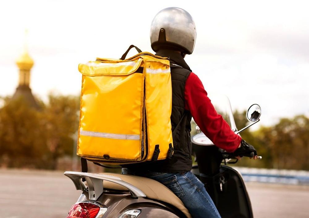 """Ilustração de um motoboy em sua moto, ao lado está escrito """"onde contratar um motoboy no RJ?"""""""