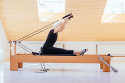 Pilates reformer eldery blond curly woma