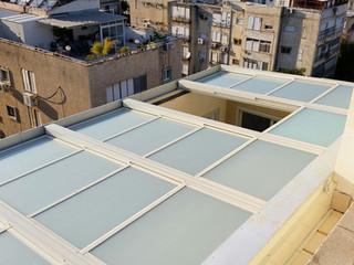 מבט עילי על פרגולה חשמלית עם חיפוי זכוכית חלבי במרפסת גג