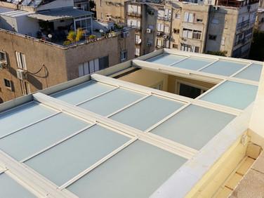 מבט עילי על גג הזזה חשמלי עם חיפוי זכוכית חלבי במרפסת גג