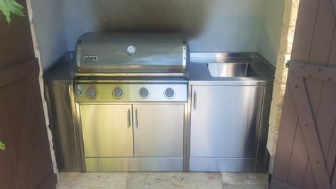 מטבח חוץ הכולל גריל גז, ארון אחסון, מקרר וכיור