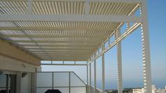 פרגולת אלומיניום לבנה על מרפסת שמש