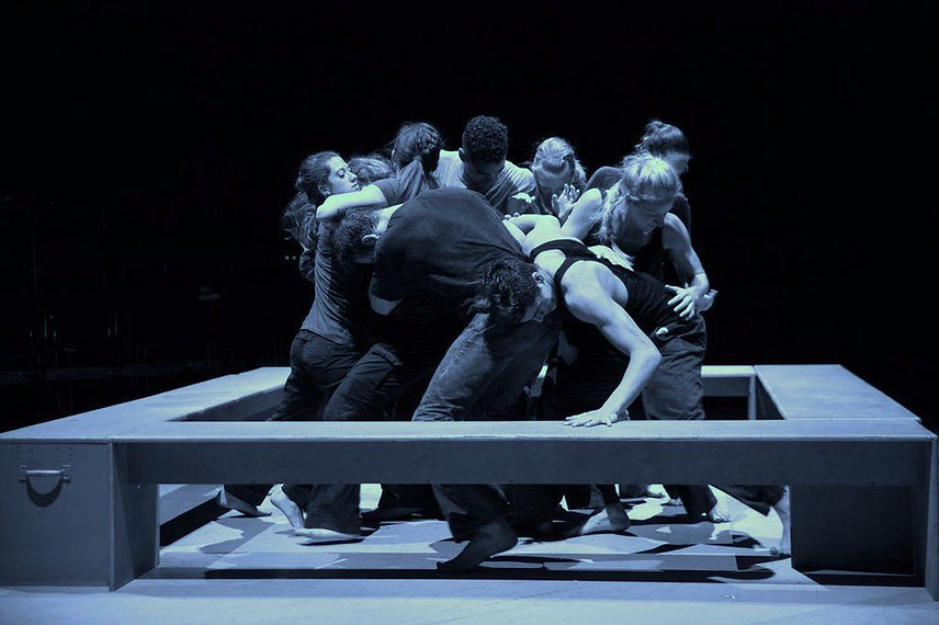 Dancers huddled around each other standing inside a box