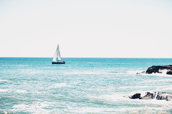 Sailing boat teal water with rock