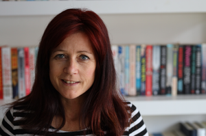 Kirsty Eyre photographed in front of a bookcase at home