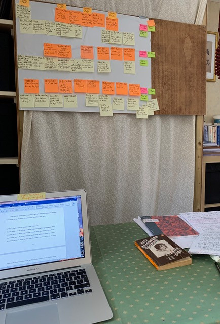 laptop on desk with board full of post-its planning novel