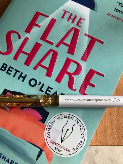 The Comedy Women in Print pen lying on a paperback copy of Beth O'Leary's The Flatshare which has the CWIP sticker on it