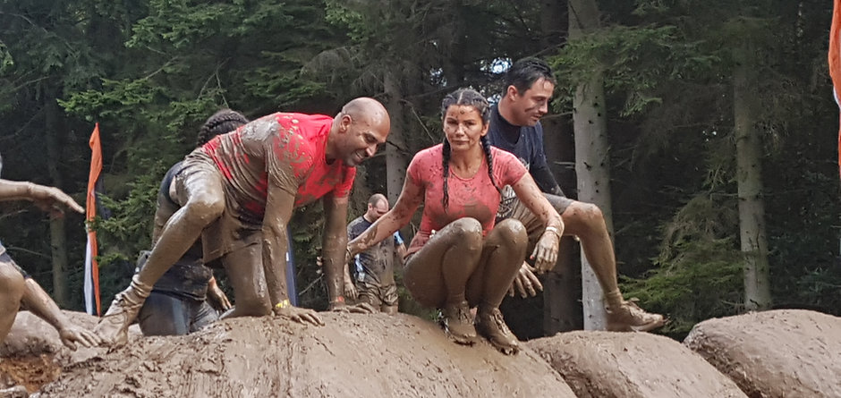 Amar being helped over a mudder hill surrounded by runners all taking part in Tough Mudder