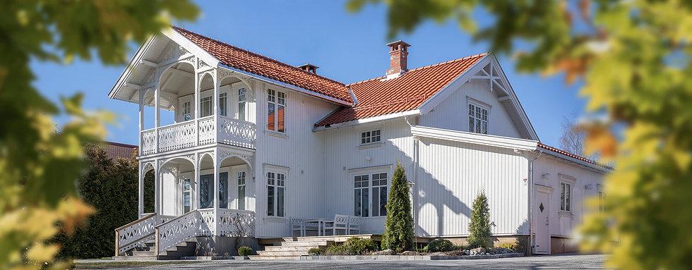 Sveitserhus, FaktorTre AS, foto, Innlandet Reklamebyrå AS, hvitt hus, fasade, fasadedetaljer. FaktorTre AS rehabiliterer og endrer fasader ved alle typer bygg. Om det skulle være behov for vindusomramming, detaljer ved overbygg og andre oppgraderinger av din boligs utseende, ta kontakt med FaktorTre AS.