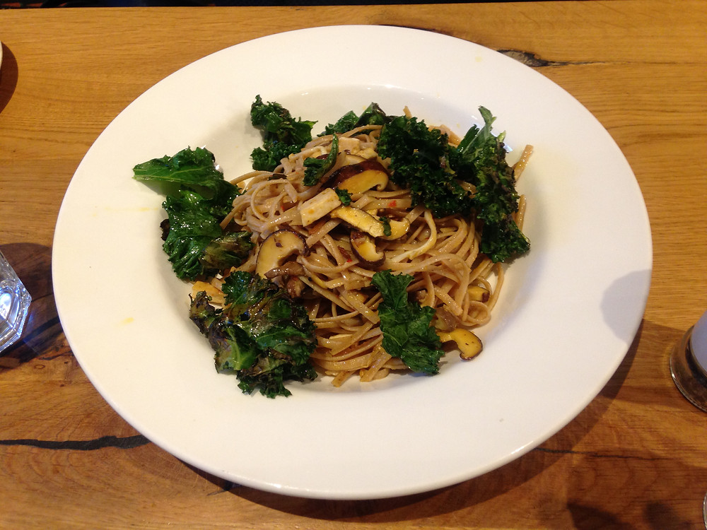 dish of linguine with mushrooms, tofu bacon and kale.