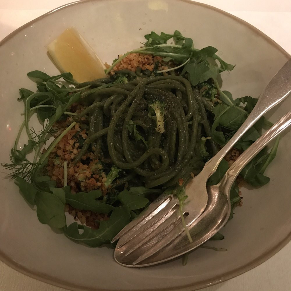 plate of fresh spinach spaghetti with kale and saffron crumbs