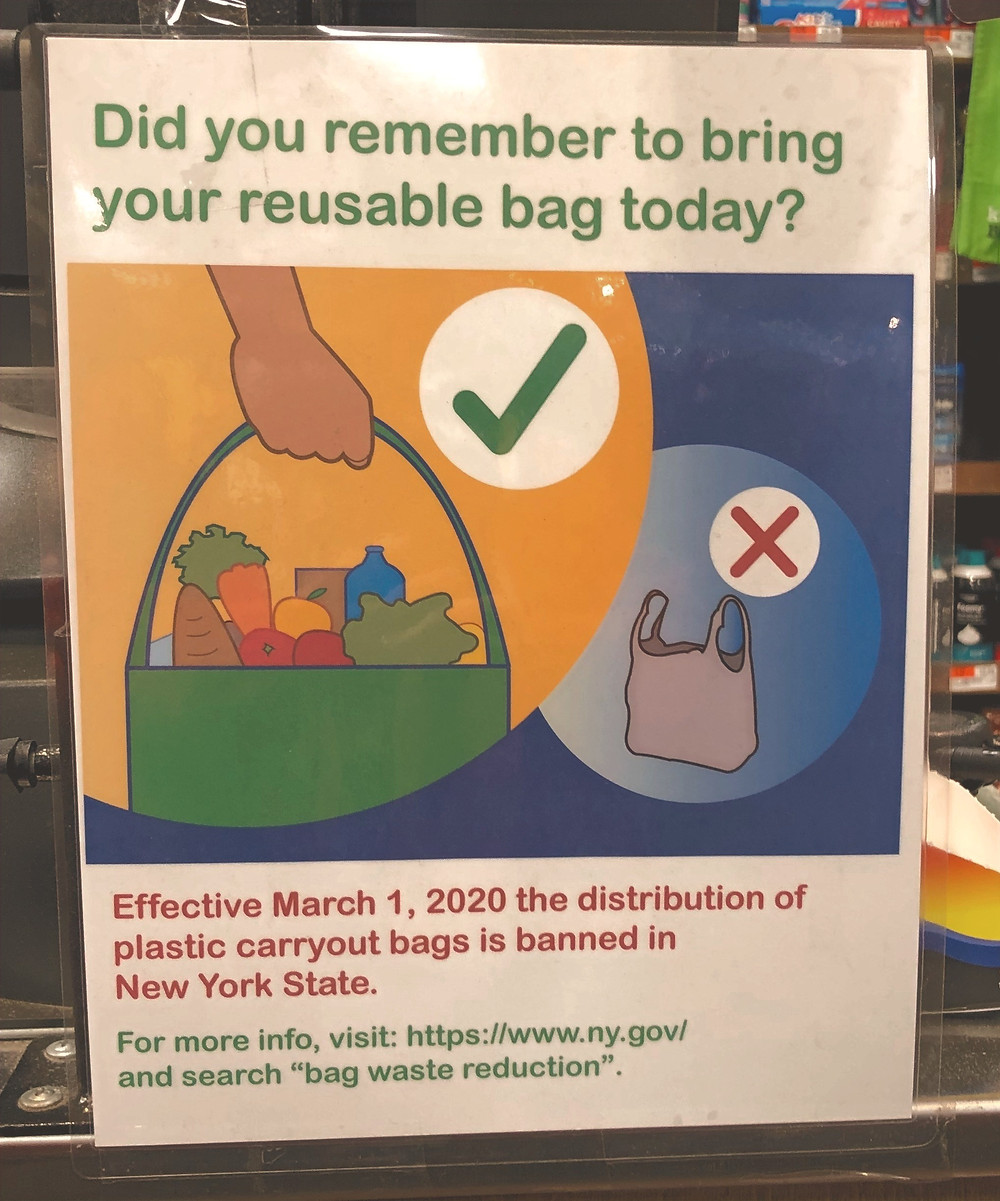 Picture of NYS flyer announcing March 1, 2020 ban on plastic bags. Shown in picture is a hand carrying a resuable bag with a green check mark filled with fruits, vegetables and other items. Next to it is a single use plastic bag with red X over it.