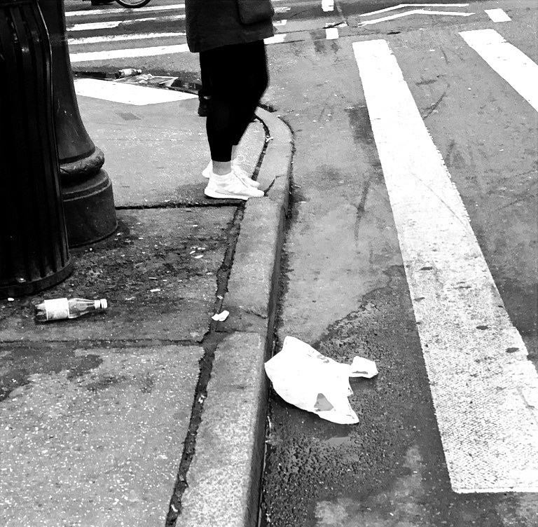Urban street scene showing a discarded plastic bag at the curb.