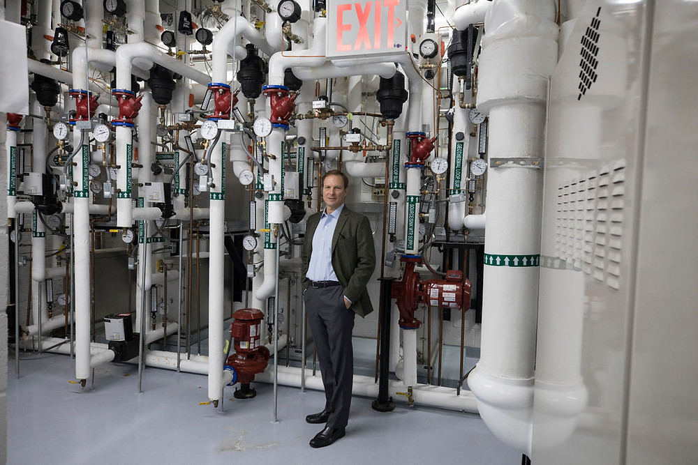 photo of Jeffrey Murphy, Jeffrey Murphy, who led the team overseeing the restoration of St. Patrick's Cathedral in Manhattan, in the geothermal plant under the church campus standing in front of the geothermal pumps.